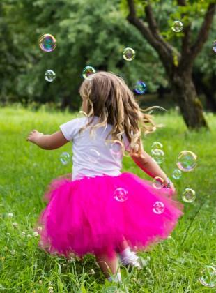 Girl chasing bubble blower