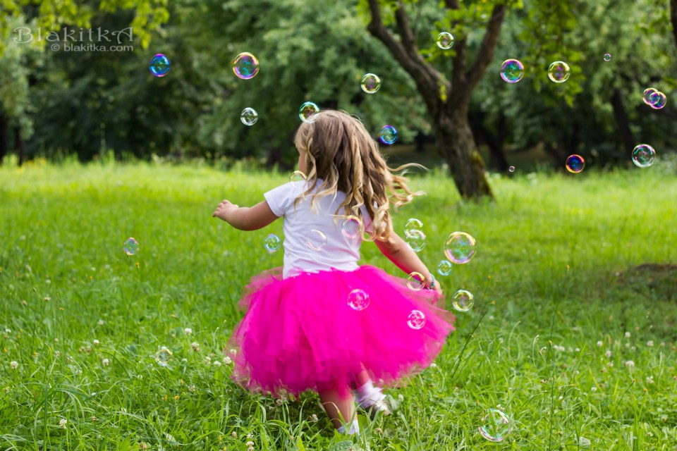 Girl chasing bubble blower