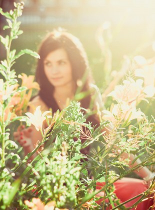 Blackhaired girl among flowers in summer