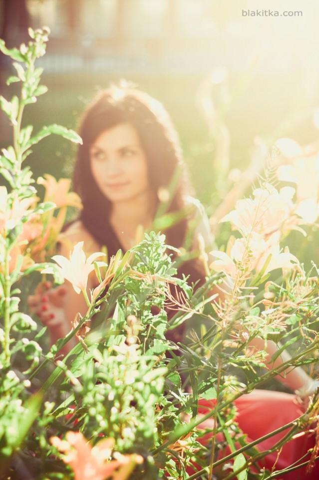 Blackhaired girl among flowers in summer