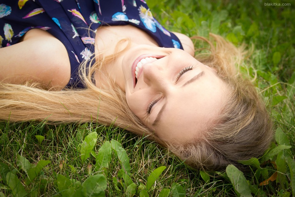 Blonde girl is laughing on the grass.