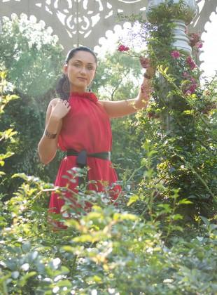 Black haired girl among rosebushes