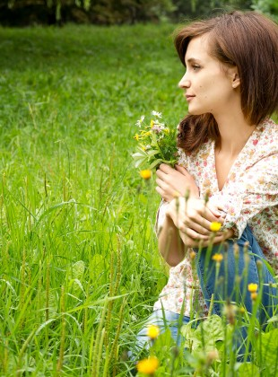 Girl in grass with bouquet of wild flowers