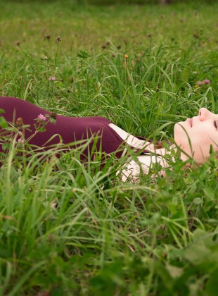 Happy pregnant woman lying in grass