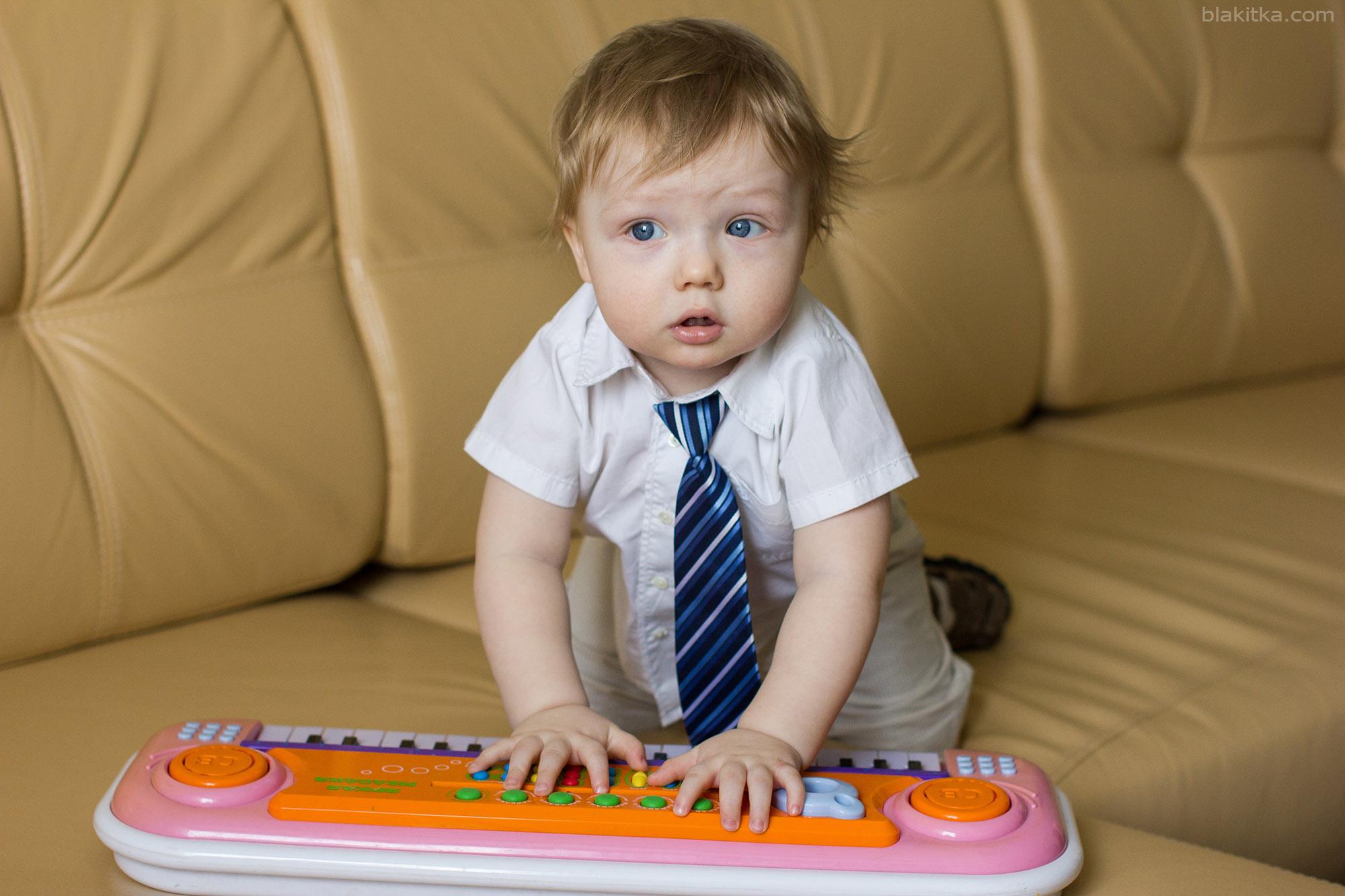 Little boy playing small piano