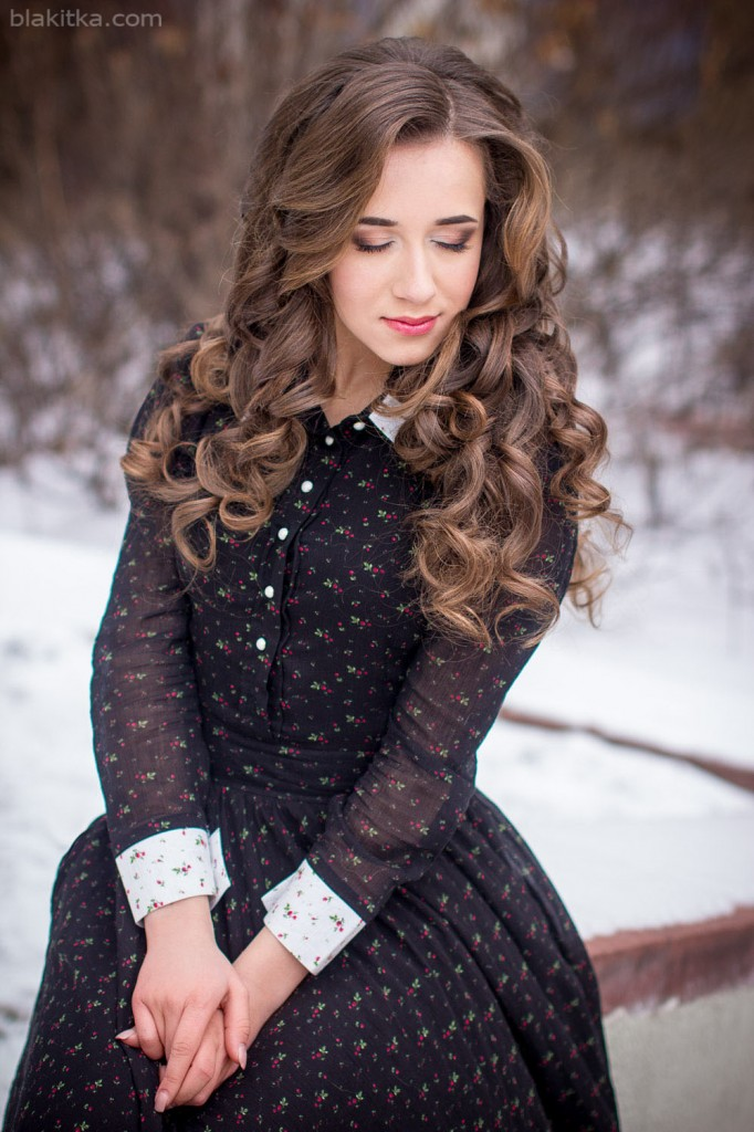 winter portrait of a beautiful girl in a long dress with snow