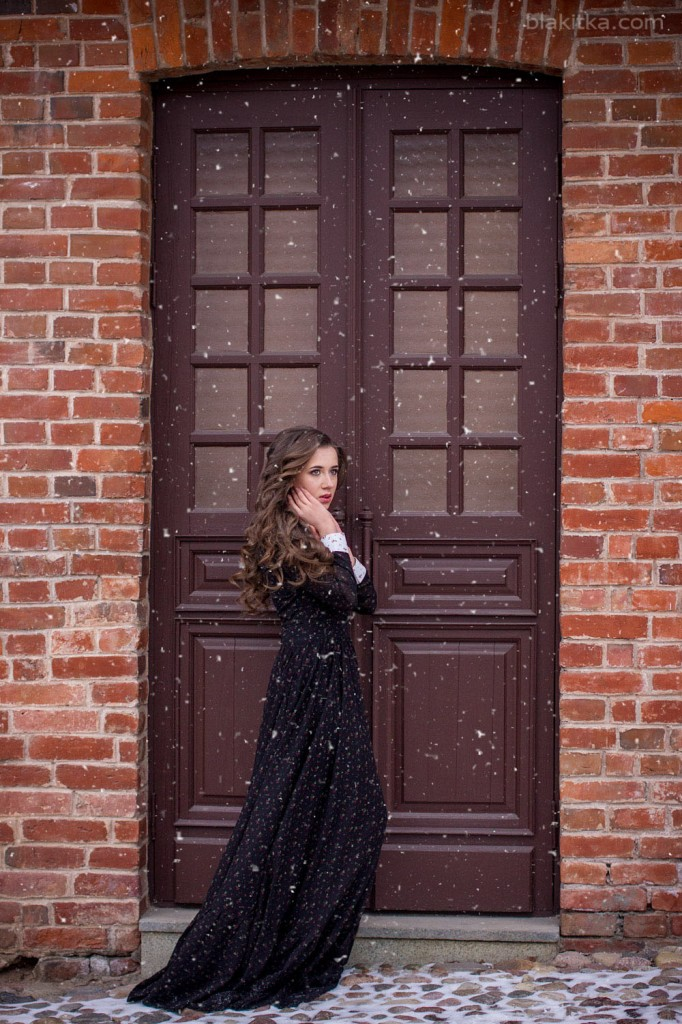 beautiful girl in a long dress with snow wind near wooden door